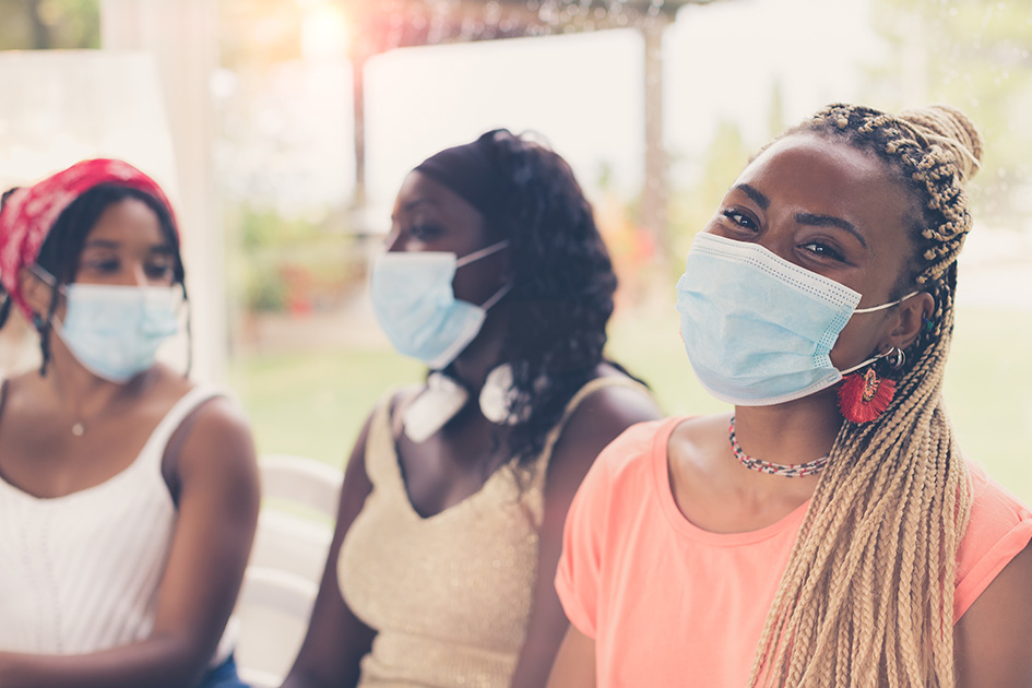 Close-up of three African American girls wearing surgical masks. 3 young women sitting together using coronavirus protection measures after or during quarantine. Concept of new normal lifestyle.